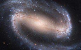 Мощный молекулярный поток втекает в спиральную галактику с перемычкой